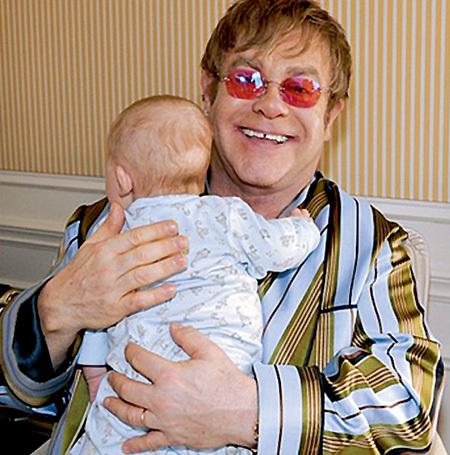 В крепких мужских руках Элтона ДЖОНА малыш чувствует себя в безопасности