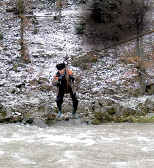 Михаил РОСОХА, сильно оттолкнувшись, долетает до середины реки, а далее рывками передвигается к другому берегу с помощью перекинутого через трос резинового шланга