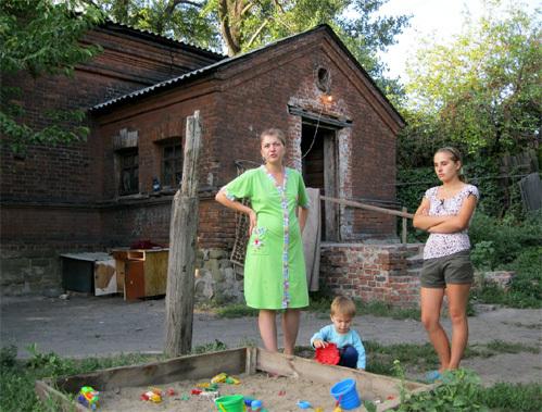 Здесь, в этом страшном бараке на окраине Донецка, жила умершая от голода девочка. На фото - молодые мамы Юля и Таня, которые вызвали скорую помощь, ужаснувшись шокирующему виду соседской девочки-мумии. Фото автора