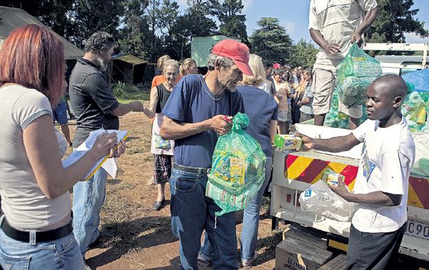 Количество белых в ЮАР, живущих за чертой бедности, постоянно растёт. Они рады продуктовым наборам, которые привозят в их гетто темнокожие благодетели. Фото: © Reuters