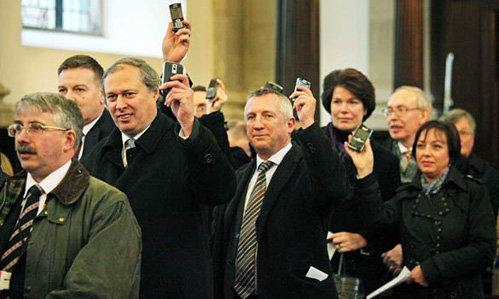 Во время службы собравшиеся в церкви люди подняли свои телефоны и ноутбуки в воздух